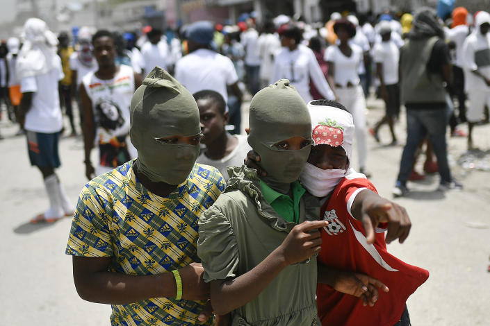 """Children with their faces covered, join a march led by Jimmy Cherizier, alias Barbecue, a former police officer who heads a gang coalition known as """"G9 Family and Allies,"""" to demand justice for slain Haitian President Jovenel Moise in La Saline neighborhood of Port-au-Prince, Haiti, Monday, July 26, 2021. Moise was assassinated on July 7 at his home. (AP Photo/Matias Delacroix)"""