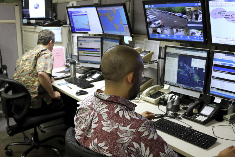 FILE - In this Dec. 1, 2017 file photo, Hawaii Emergency Management Agency officials work at the department's command center in Honolulu. Nearly 40 terrifying minutes passed between the time the Hawaii agency fired off a bogus alert about an incoming missile over the weekend and the moment the notice was canceled. The confusion _ and panic _ has raised questions about whether any state should be responsible for the notification _ especially as Washington and North Korea trade insults and threats. (AP Photo/Caleb Jones, File)