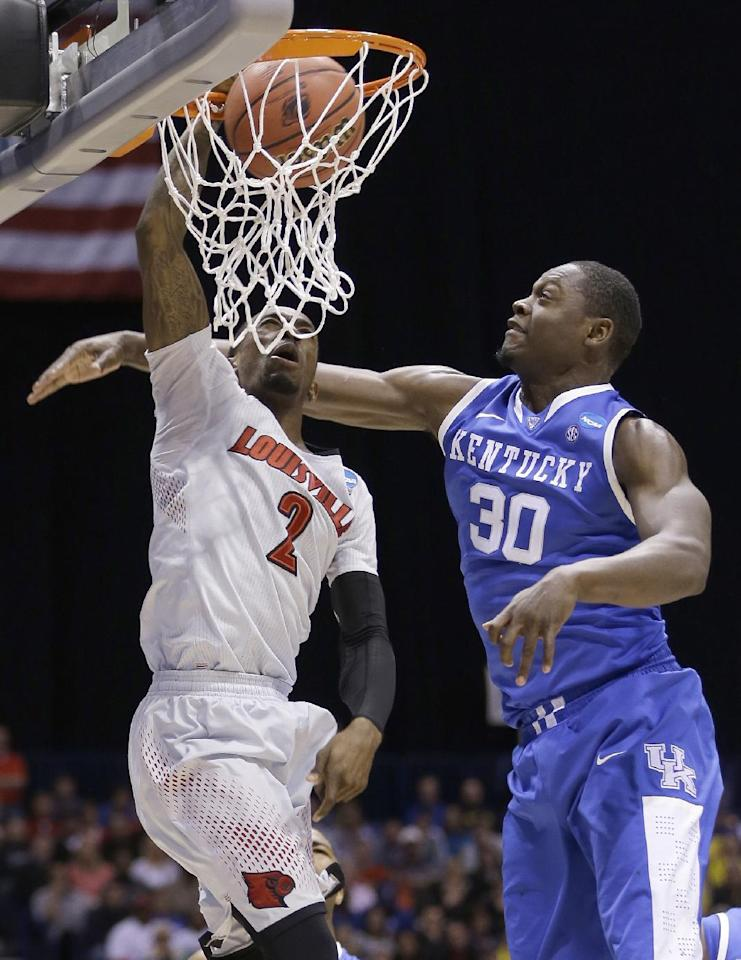 Louisville's Russ Smith (2) dunks over Kentucky's Julius Randle (30) during the first half of an NCAA Midwest Regional semifinal college basketball tournament game Friday, March 28, 2014, in Indianapolis. (AP Photo/David J. Phillip)