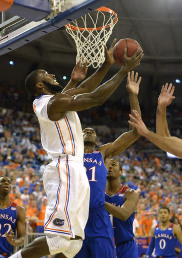 Florida center Patric Young (4) goes for two from under the basket as Kansas center Joel Embiid (21) is unable to block the shot during the first half of an NCAA college basketball game Tuesday, Dec. 10, 2013 in Gainesville, Fla. (AP Photo/Phil Sandlin)