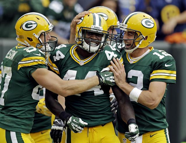 Green Bay Packers' Aaron Rodgers (12) and Jordy Nelson (87) congratulate James Starks (44) after Stark's 32-heard touchdown run during the second half of an NFL football game against the Washington Redskins Sunday, Sept. 15, 2013, in Green Bay, Wis. (AP Photo/Morry Gash)