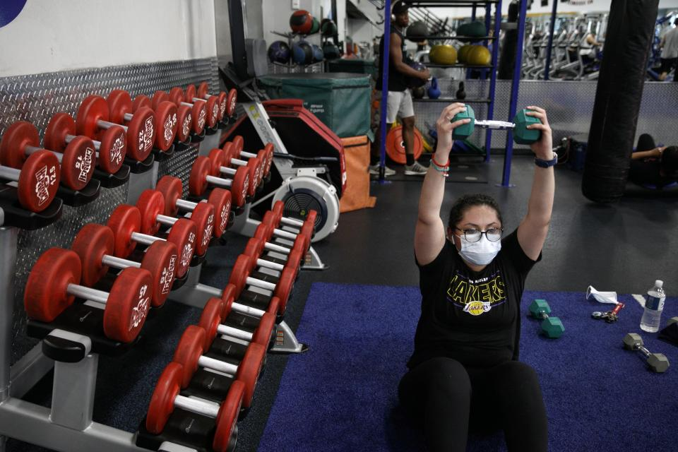 Mayra Miranda, 34, wears a mask while exercising at a gym in Los Angeles. Friday, June 26, 2020. With the coronavirus surging, at least four California counties on Friday paused or prepared to backtrack on their reopening plans in a bid to halt the spread of the virus. (AP Photo/Jae C. Hong)