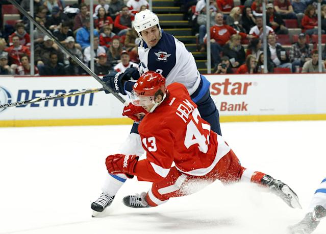 Winnipeg Jets defenseman Adam Pardy (2) checks Detroit Red Wings center Darren Helm (43) during the second period of an NHL hockey game in Detroit, Tuesday, Nov. 12, 2013. (AP Photo/Paul Sancya)