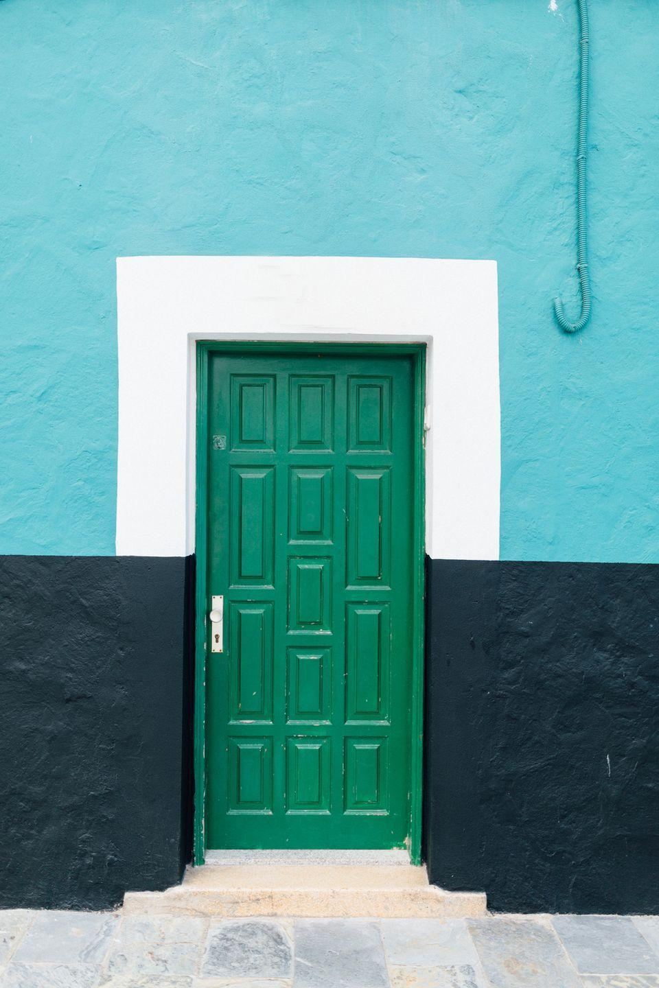 <p>Cool colors come together around a bright green door.</p>