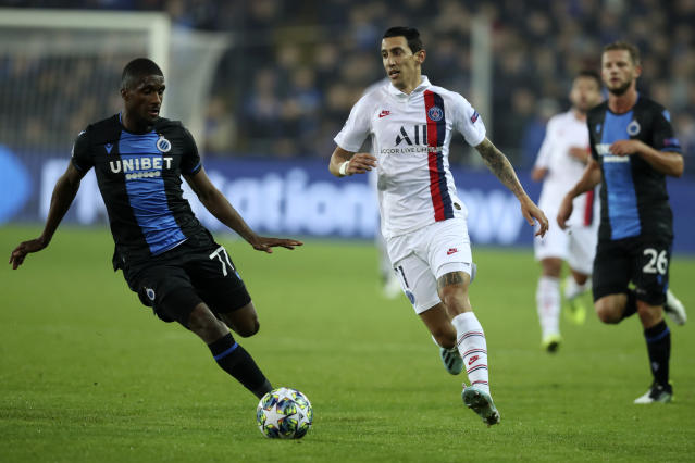 PSG's Angel Di Maria, center, vies for the ball with Brugge's Clinton Mata, left, during a Champions League Group A soccer match between Club Brugge and Paris Saint Germain at the Jan Breydel stadium in Bruges, Belgium, Tuesday, Oct. 22, 2019. (AP Photo/Francisco Seco)