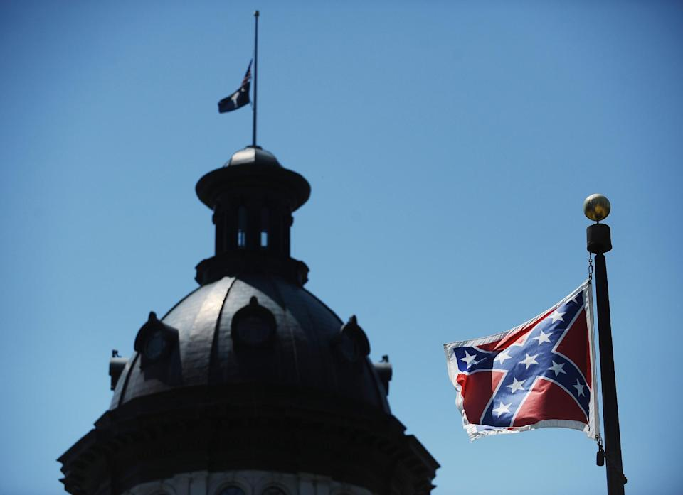 FILE - In a Friday, June 19, 2015 file photo, the Confederate flag flies near the South Carolina Statehouse, in Columbia, S.C. For 15 years, South Carolina lawmakers refused to consider removing the Confederate flag from Statehouse grounds, but opinions changed within five days of the massacre of nine people at Emanuel African Methodist Episcopal church in Charleston, as a growing tide of Republicans joined the call to remove the battle flag from a Confederate monument in front of the Statehouse and put it in a museum., File (AP Photo/Rainier Ehrhardt, File)