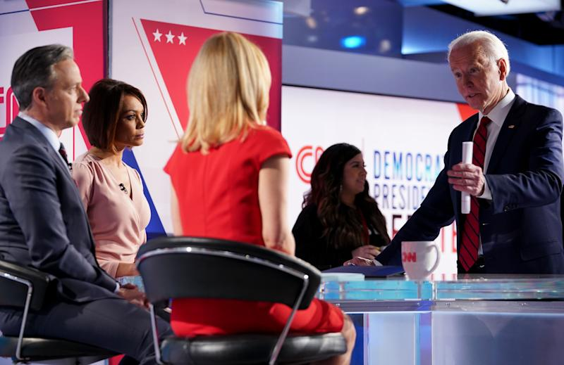 Democratic presidential hopeful former US vice president Joe Biden talks with moderators (L-R) Univision's journalist Ilia Calderon, CNN chief Washington correspondent Jake Tapper and CNN political correspondent Dana Bash at the end of the 11th Democratic Party 2020 presidential debate in a CNN Washington Bureau studio in Washington, DC on March 15, 2020. (Photo by MANDEL NGAN / AFP) (Photo by MANDEL NGAN/AFP via Getty Images)