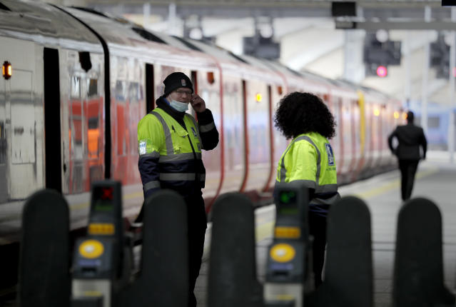 Station staff work at a quiet quiet Waterloo Station in London during rush hour, Wednesday, May 13, 2020, as the country continues in lockdown to help stop the spread of coronavirus. Some of the coronavirus lockdown measures are being relaxed in England on Wednesday, with those workers who are unable to work from home, such as those in construction and manufacturing, encouraged to return to work. (AP Photo/Kirsty Wigglesworth)