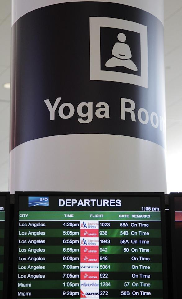 In this Friday, Jan. 27, 2012 photo, a sign advertising San Francisco International Airport's new Yoga Room is posted above a departures board, in San Francisco. The quiet, dimly lit studio officially opened last week in a former storage room just past the security checkpoint at SFO's Terminal 2. Airport officials believe the 150-square-foot room with mirrored walls is the world's first airport yoga studio, said spokesman Mike McCarron. (AP Photo/Paul Sakuma)