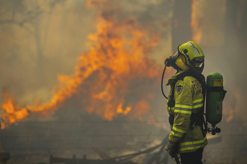 Firefighter Adam Brown from FRNSW protects properties along Glenthorne Rd in South Taree from an out of control bushfire.