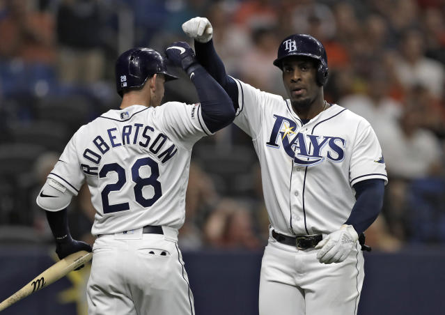Tampa Bay Rays' Yandy Diaz celebrates his home run off Houston Astros starting pitcher Gerrit Cole with Daniel Robertson (28) during the sixth inning of a baseball game Friday, March 29, 2019, in St. Petersburg, Fla. (AP Photo/Chris O'Meara)