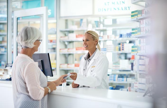 Shot of a young pharmacist helping an elderly customer