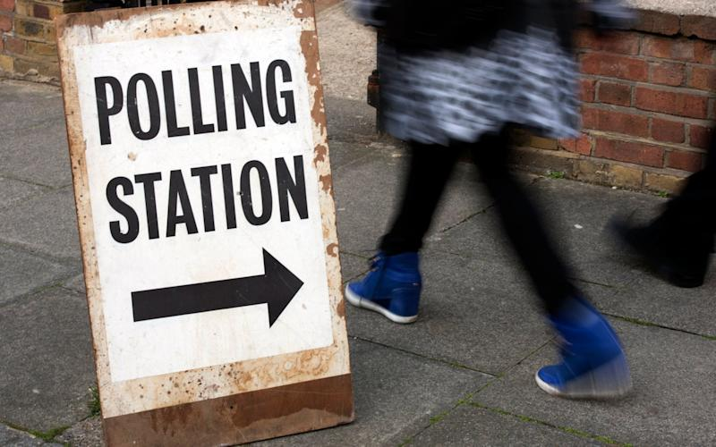 People pass a polling station sign in Brixton, south west London - Credit: HANNAH MCKAY
