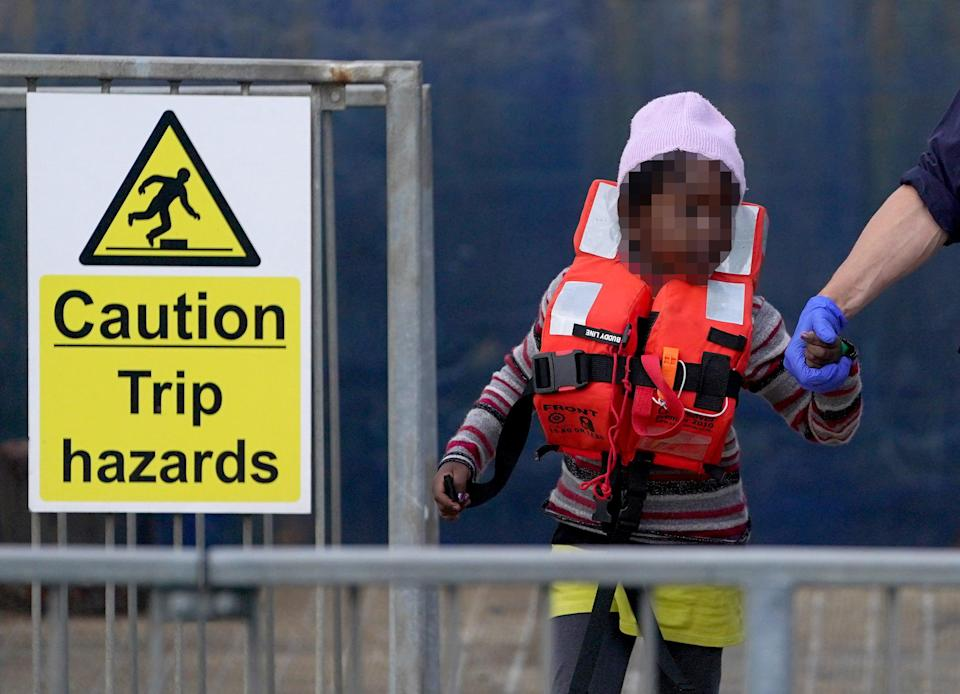 A young girl is escorted by a Border Force officer as a group of people thought to be migrants are brought in to Dover, Kent (PA) (PA Wire)