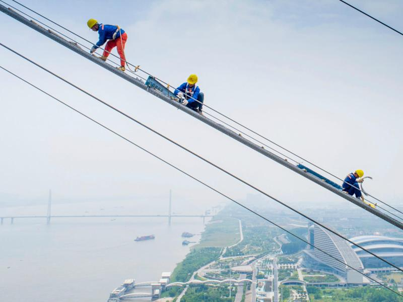 Workers on a suspension bridge being constructed over the Yangtze River in Wuhan in China's central Hubei province. The East has the opportunity to succeed where the West has failed: Getty