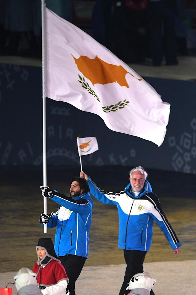 <p>Cyprus flagbearer Dinos Lefkaritis leads the delegation parade during the opening ceremony of the Pyeongchang 2018 Winter Olympic Games at the Pyeongchang Stadium on February 9, 2018. (Photo by ROBERTO SCHMIDT/AFP/Getty Images) </p>