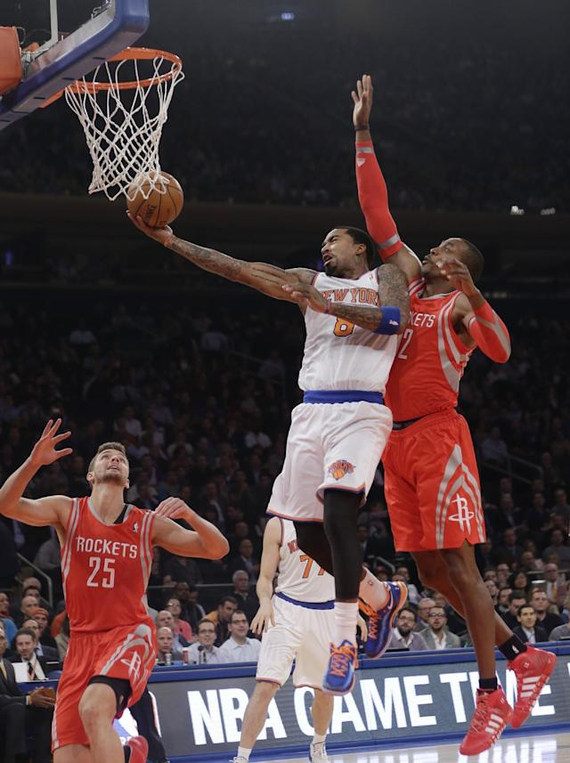 New York Knicks' J.R. Smith (8) drives past Houston Rockets' Dwight Howard (12) and Chandler Parsons (25) during the first half of an NBA basketball game Thursday, Nov. 14, 2013, in New York. (AP Photo/Frank Franklin II)
