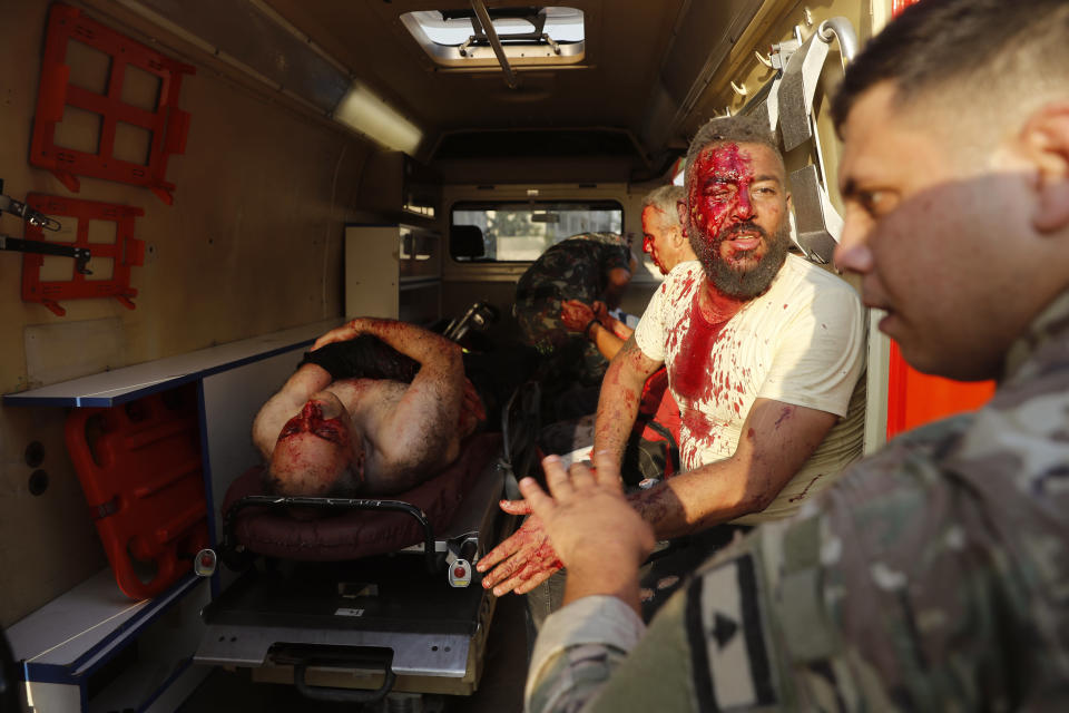 A Lebanese soldier, right, checks on injured men who sit inside an ambulance at the explosion scene that hit the seaport of Beirut, Lebanon, Tuesday, Aug. 4, 2020. (AP Photo/Hussein Malla)
