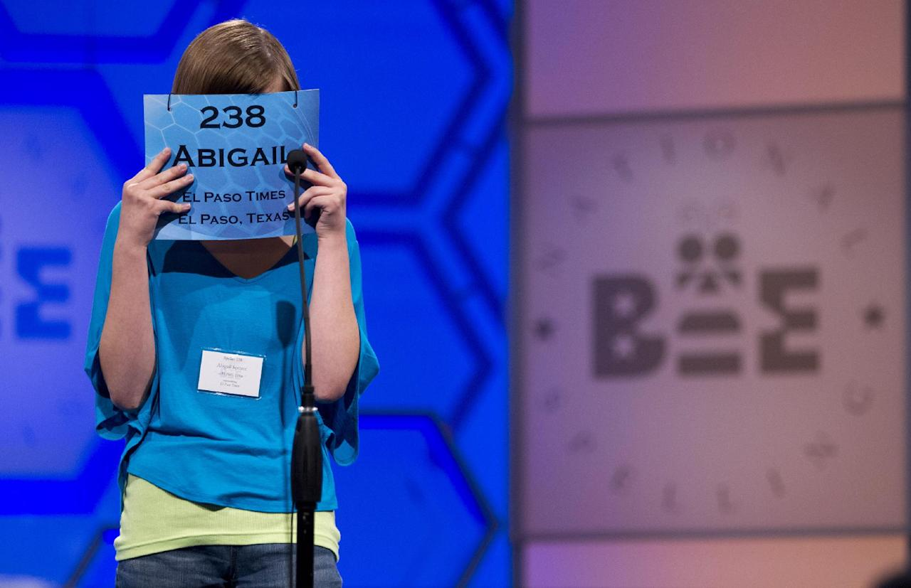Abigail Violet Spitzer, of El Paso, Texas, covers her face as she concentrates during the semifinal round of the National Spelling Bee, Thursday, May 31, 2012, in Oxon Hill, Md. (AP Photo/Evan Vucci)