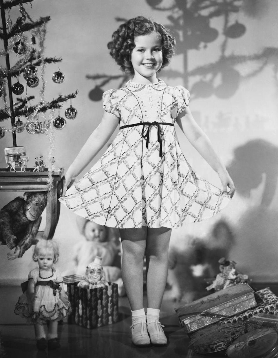 <p>Child star Shirley Temple (<em>Curly Top</em>) models a dress for a 1936 holiday ad. Earlier that year, Temple had starred in four movies, including <em>Captain January, Poor Little Rich Girl, Dimples, and Stowaway. </em></p>