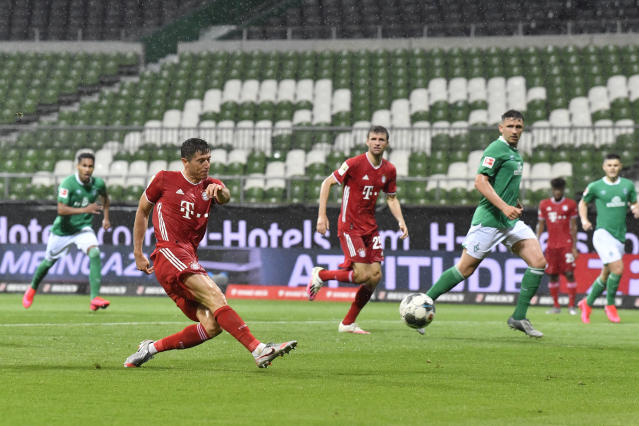 Bayern's Robert Lewandowski, left, scores his side's opening goal during the German Bundesliga soccer match between Werder Bremen and Bayern Munich in Bremen, Germany, Tuesday, June 16, 2020. Because of the coronavirus outbreak all soccer matches of the German Bundesliga take place without spectators. (AP Photo/Martin Meissner, Pool)