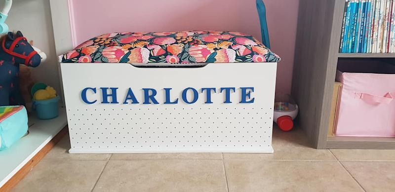 A Kmart toy box with a colourful bench cushion and the name 'Charlotte' in wooden letters on the front
