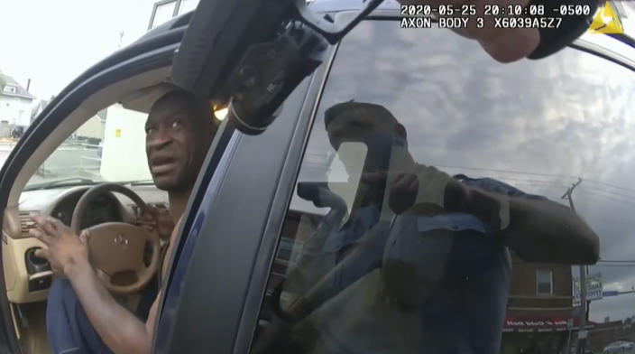 In this image from police body cam video, a Minneapolis police officer approaches George Floyd with a gun drawn, on May 25, 2020, outside Cup Foods in Minneapolis, as it is shown Wednesday, March 31, 2021, in the trial of former Minneapolis police Officer Derek Chauvin, in Floyd's death, at the Hennepin County Courthouse in Minneapolis. (Court TV via AP, Pool)