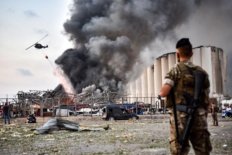 EDITORS NOTE: Graphic content / Lebanese army soldiers stand while behind a helicopter puts out a fire at the scene of an explosion at the port of Lebanon's capital Beirut on August 4, 2020. (Photo by STR / AFP) (Photo by STR/AFP via Getty Images) (Photo: STR via Getty Images)
