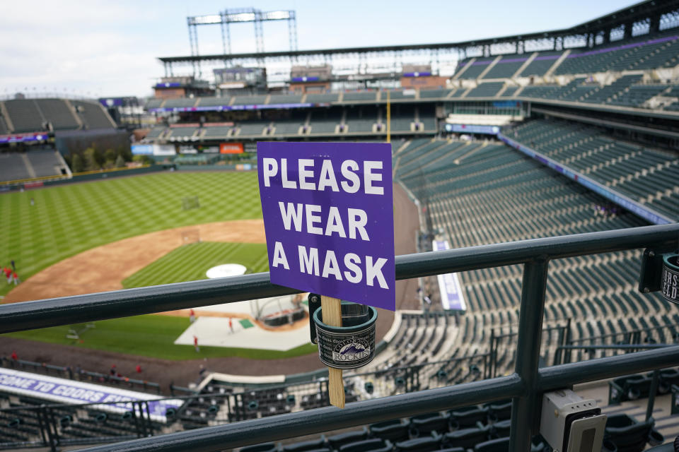 A COVID-19 sign urging fans to wear their masks is threaded through a drink holder in the upper deck of Coors Field before the Colorado Rockies host the Cincinnati Reds in a baseball game late Thursday, May 13, 2021, in Denver. (David Zalubowski/AP)