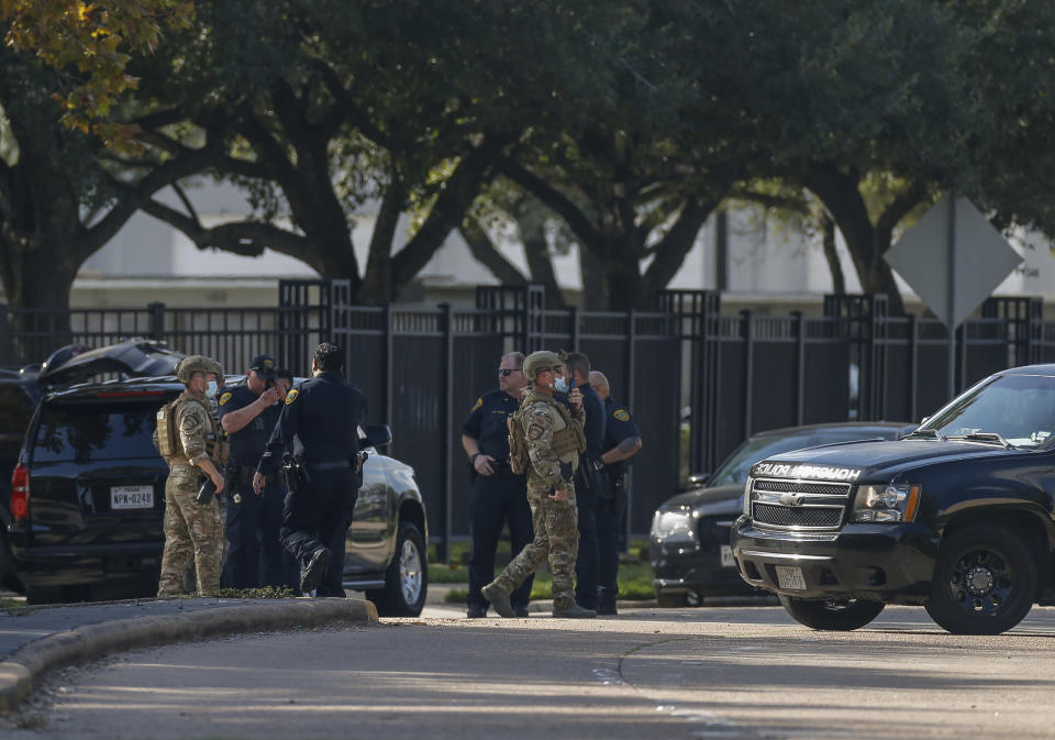 Houston Police officers investigate the scene of an officer-involved shooting at an apartment complex on Tuesday, Oct. 20, 2020, in Houston. Two Houston officers were shot before a SWAT team was dispatched to the scene, where the suspected shooter was arrested, authorities said. (Godofredo A. Vásquez / Houston Chronicle via AP)