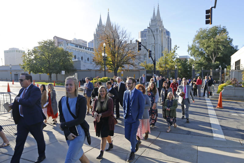 FILE - In this Saturday, Oct. 5, 2019, file photo, people arrive for The Church of Jesus Christ of Latter-day Saints' twice-annual church conference, in Salt Lake City. For the first time in more than 60 years, top leaders from The Church of Jesus Christ of Latter-day Saints will deliver speeches at the faith's signature conference this weekend without anyone watching in the latest illustration of how the coronavirus pandemic is altering worship practices around the world. The twice-yearly conference normally brings some 100,000 people to the church conference center in Salt Lake City to watch five sessions over two days. This event, though, will be only a virtual one. (AP Photo/Rick Bowmer, File)