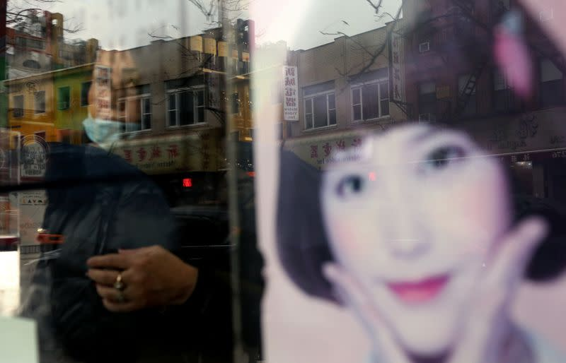 A woman who prefers to remain anonymous looks through a window in Chinatown in New York