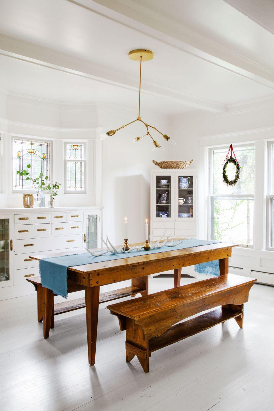 "<p>This designer keeps the dining room table in her <a href=""https://www.countryliving.com/home-design/house-tours/g2780/jennaea-gearhart-white-christmas-decor/"" rel=""nofollow noopener"" target=""_blank"" data-ylk=""slk:historic Tudor house"" class=""link rapid-noclick-resp"">historic Tudor house</a> simple for the season with a blue runner, brass candle holders, and antlers.</p><p><a class=""link rapid-noclick-resp"" href=""https://go.redirectingat.com?id=74968X1596630&url=https%3A%2F%2Fwww.etsy.com%2Fmarket%2Fbrass_candle_holder&sref=https%3A%2F%2Fwww.countryliving.com%2Fdiy-crafts%2Fg644%2Fchristmas-tables-1208%2F"" rel=""nofollow noopener"" target=""_blank"" data-ylk=""slk:SHOP BRASS CANDLE HOLDERS"">SHOP BRASS CANDLE HOLDERS</a></p>"