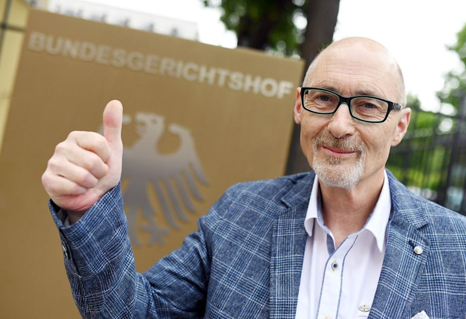 25 May 2020, Baden-Wuerttemberg, Karlsruhe: Herbert Gilbert, plaintiff against the car manufacturer VW in the diesel scandal, is standing before the Federal Court of Justice (BGH), before the beginning of the pronouncement of judgement, at a sign with a federal eagle and the lettering Bundesgerichtshof. According to the ruling, Volkswagen is in principle obliged to pay damages to car owners affected by the diesel scandal. Plaintiff buyers, who want the money for their car back, must however have the kilometres driven credited, the Federal High Court (BGH) in Karlsruhe decided on Monday. Photo: Uli Deck/dpa (Photo by Uli Deck/picture alliance via Getty Images)