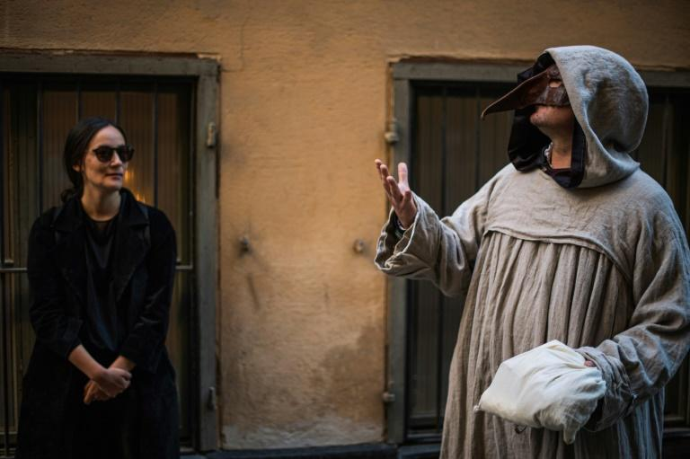 """Tour guide Mike Anderson (R) takes visitors on a """"plague walk"""" in Stockholm's Old Town in May 2020 (AFP Photo/Jonathan NACKSTRAND)"""