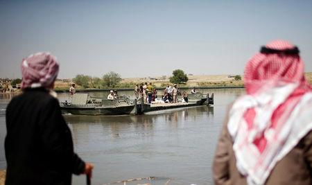 Displaced Iraqis wait for a military boat to cross the Tigris river after the bridge has been temporarily closed, south of Mosul