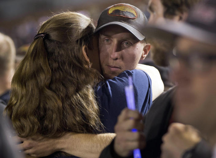 FILE - In this July 2, 2013 file photo, firefighter Brendan McDonough embraces a mourner near the end of a candlelight vigil in Prescott, Ariz. The wildfire that began with a lightning strike and caused little immediate concern because of its remote location and small size quickly blazed into an inferno, leading officials to rapidly order more resources in the hours before flames killed 19 members of an elite Hotshot crew, according to a report released Monday, July 15, 2013. (AP Photo/Julie Jacobson, File)