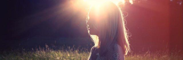 woman outside in field with sun flare behind her