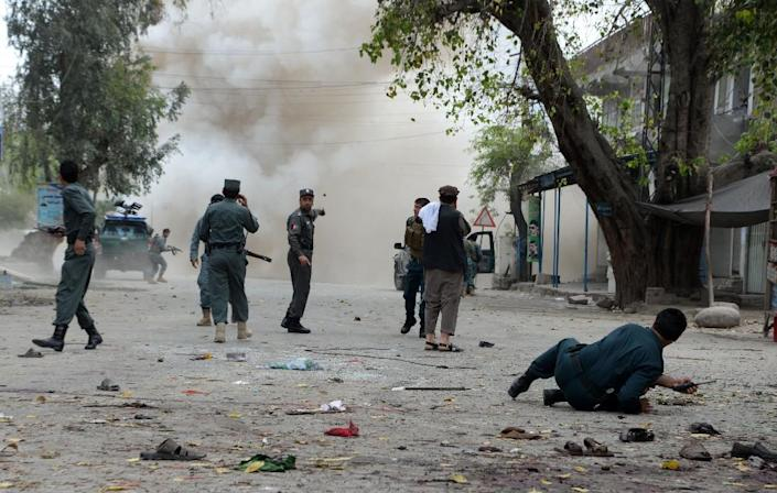 Security personnel look on after a second explosion following a suicide attack outside a bank in the eastern Afghan city of Jalalabad on April 18, 2015 (AFP Photo/Noorullah Shirzada)