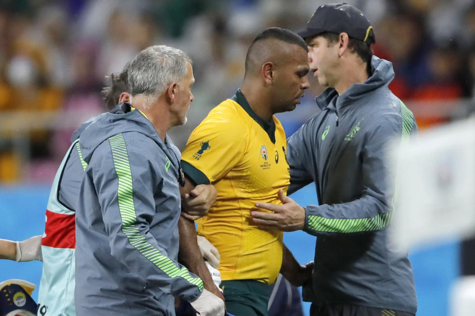 """FILE - In this Oct. 11, 2019,file photo, Australia's Kurtley Beale, center, is assisted from the field after suffering a head injury during the Rugby World Cup Pool D game at Shizuoka Stadium Ecopa between Australia and Georgia in Shizuoka, Japan. A """"shadow trial"""" of advanced eye-tracking technology will be conducted in the Trans-Tasman Super Rugby tournament in Australia and New Zealand as part of World Rugby's bid to tackle head injuries by improving the detection of concussion. (AP Photo/Christophe Ena, File)"""
