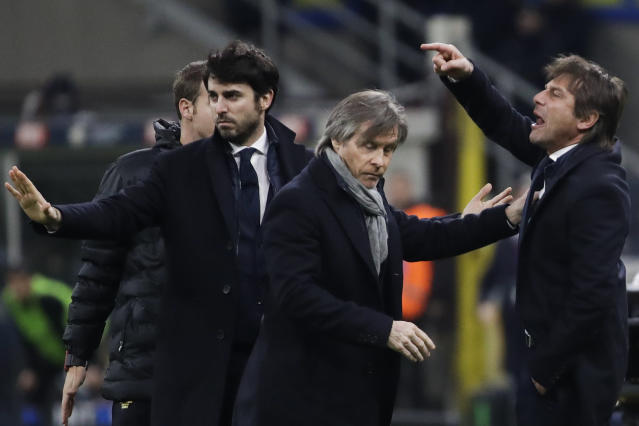 Inter Milan's head coach Antonio Conte, right, argues with referee Gianpaolo Calvarese after one of his players was shown a yellow card during an Italian Cup soccer match between Inter Milan and Napoli at the San Siro stadium, in Milan, Italy, Wednesday, Feb. 12, 2020. (AP Photo/Luca Bruno)