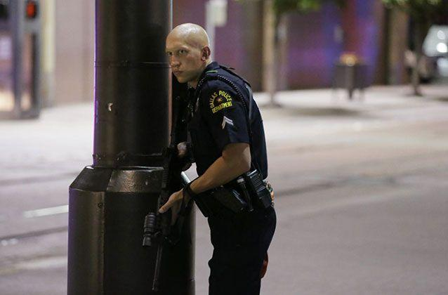 A Dallas policeman keeps watch on a street in downtown Dallas, Thursday, July 7, 2016, following reports that shots were fired during a protest over two recent fatal police shootings of black men. Picture: AP/LM Otero