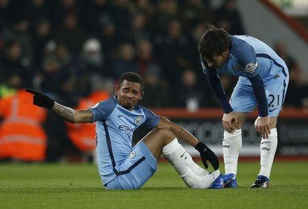 Manchester City's Gabriel Jesus sits after sustaining an injury as David Silva looks on