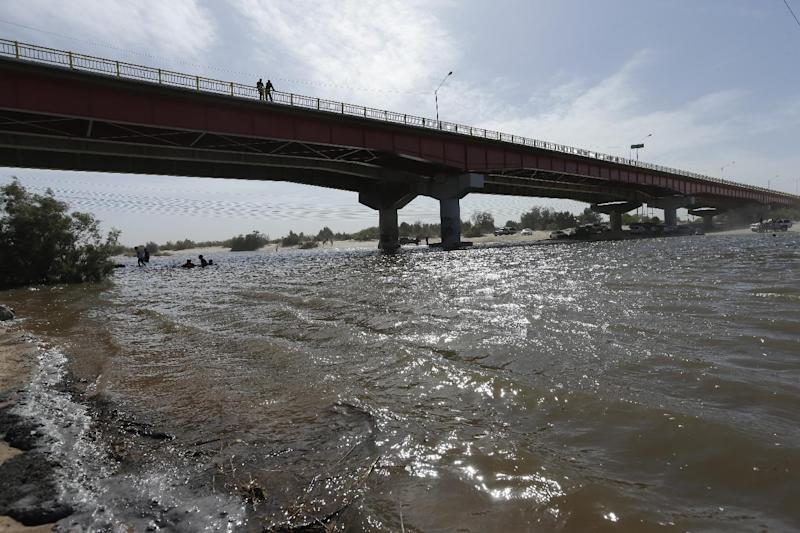 Water flows in a usually dry riverbed Wednesday, March 26, 2014, in San Luis Rio Colorado, Mexico. Colorado River water has begun pouring over a barren delta near the U.S.-Mexico border, the result of a landmark bi-national agreement being celebrated Thursday. (AP Photo/Gregory Bull)