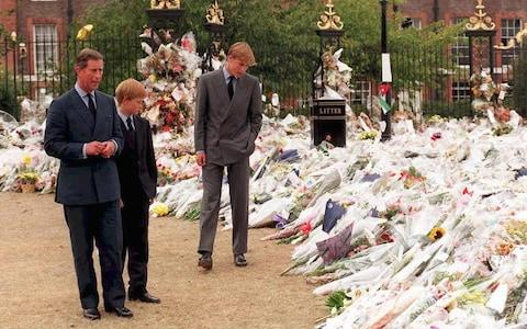 The Prince of Wales and Princes William and Harry inspect thousands of bouquets of floral tributes to their mother Diana, Princess of Wales, outside Kensington Palace on September 5, 1997. - Credit: AFP