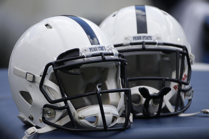 A pair of Penn State football helmets sit on a trainer's table on the sidelines during an NCAA college football game between the Penn State and the Temple in State College, Pa., Saturday, Nov. 15, 2014. (AP Photo/Gene J. Puskar)