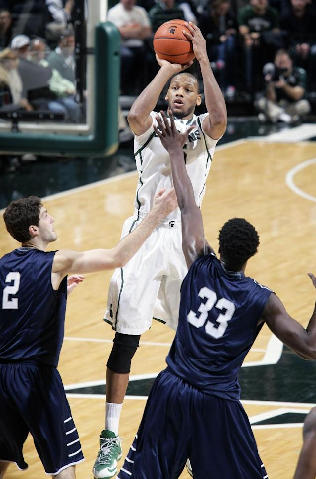 CORRECTS LOCATION TO EAST LANSING FROM AUBURN HILLS - Michigan State's Adreian Payne, center, shoots against North Florida's Beau Beech (2) and Romel Banks (33) during the first half of an NCAA college basketball game, Tuesday, Dec. 17, 2013, in East Lansing, Mich. (AP Photo/Al Goldis)