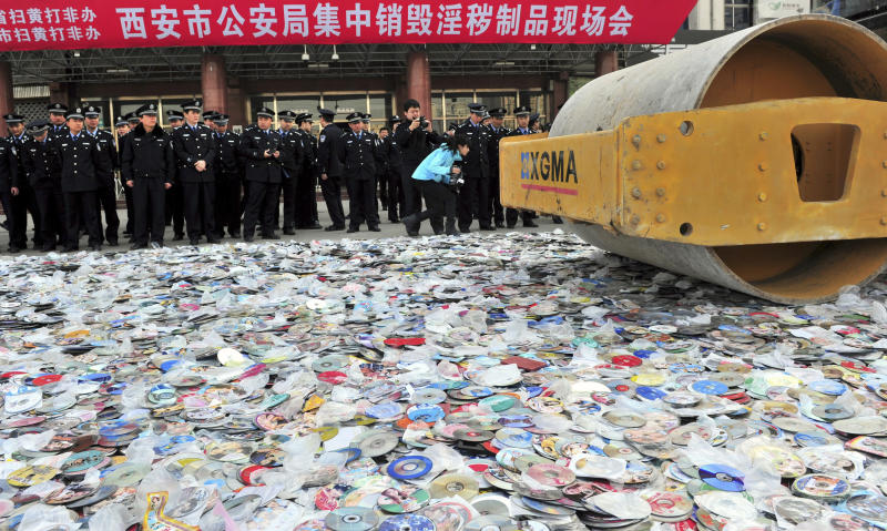Police officers look on as a road roller is used to destroy confiscated pornographic DVDs and pirated publications in Xi'an, Shaanxi province March 17, 2011. Local police destroyed about 300,000 pornographic DVDs and pirated publications on Thursday during a campaign to stamp out porn and pirated products, local media reported. REUTERS/China Daily (CHINA - Tags: CRIME LAW MEDIA IMAGES OF THE DAY) CHINA OUT. NO COMMERCIAL OR EDITORIAL SALES IN CHINA