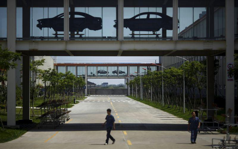 File photo of employees walking under a car assembly line at Geely Automobile Corporation in Cixi