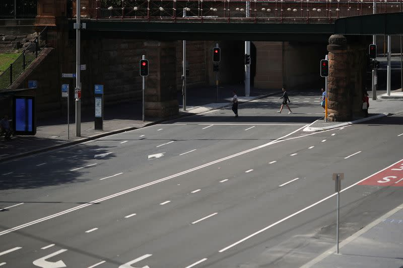 People walk by an almost empty street during a workday following the implementation of stricter social-distancing and self-isolation rules to limit the spread of the coronavirus disease (COVID-19) in Sydney